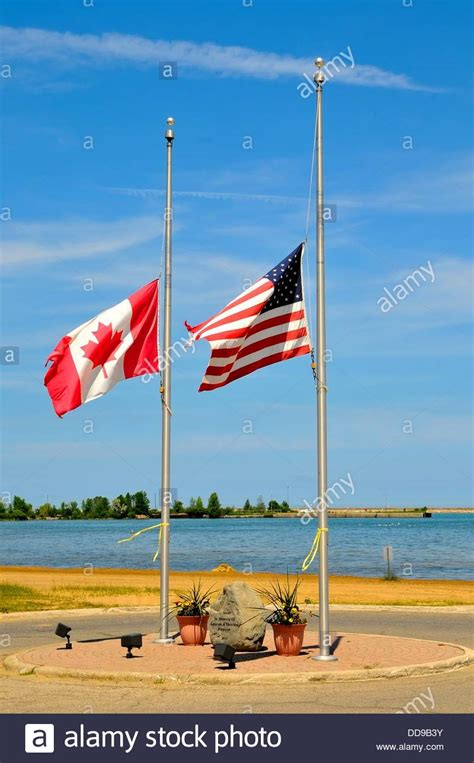 American and Canadian flags fly together at half mast